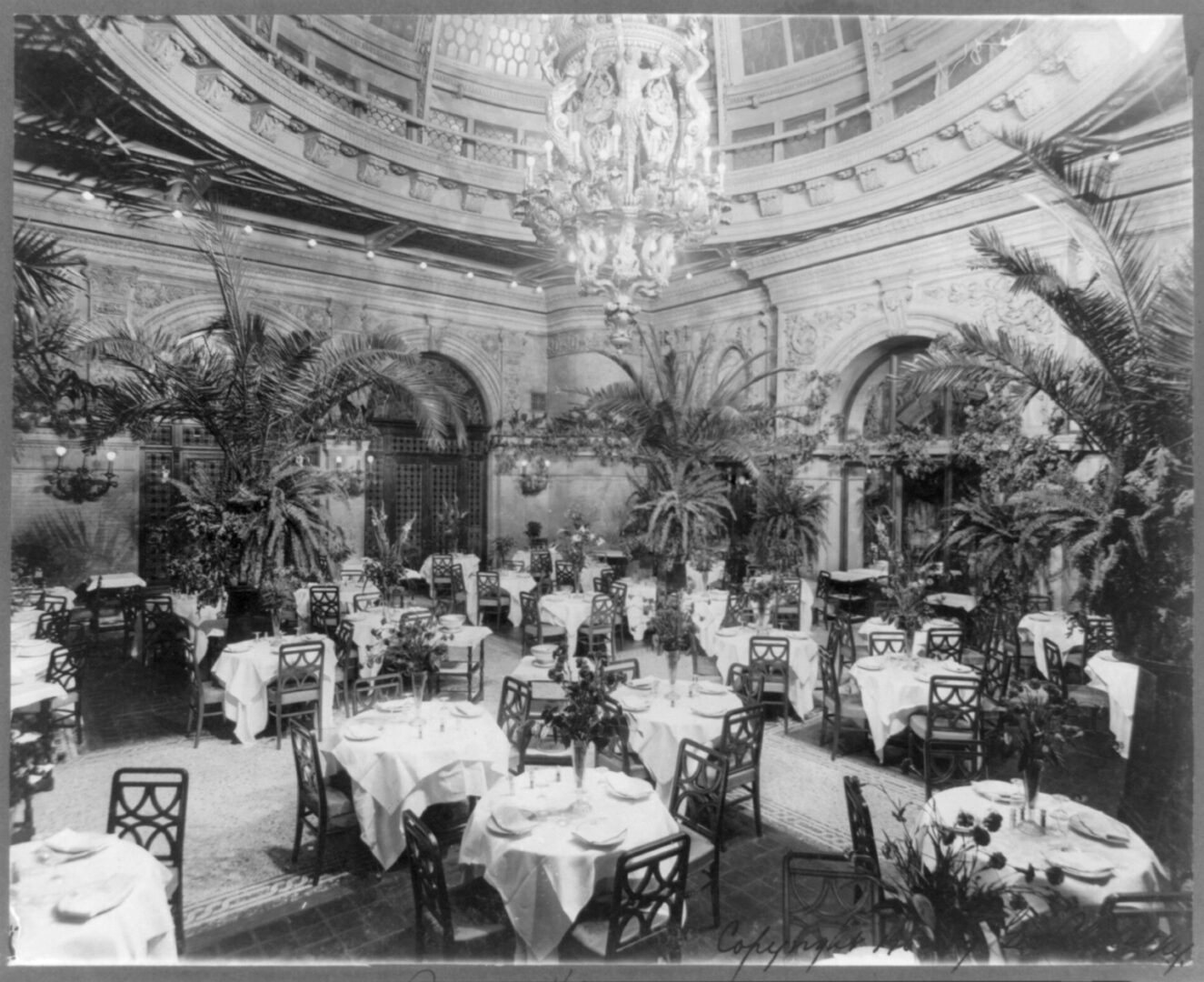 "The Waldorf-Astoria's ornate Palm Room, in which patrons<br>were required to wear formal attire,<br>was located at one end of the hotel's legendary<br>""Peacock Alley."""